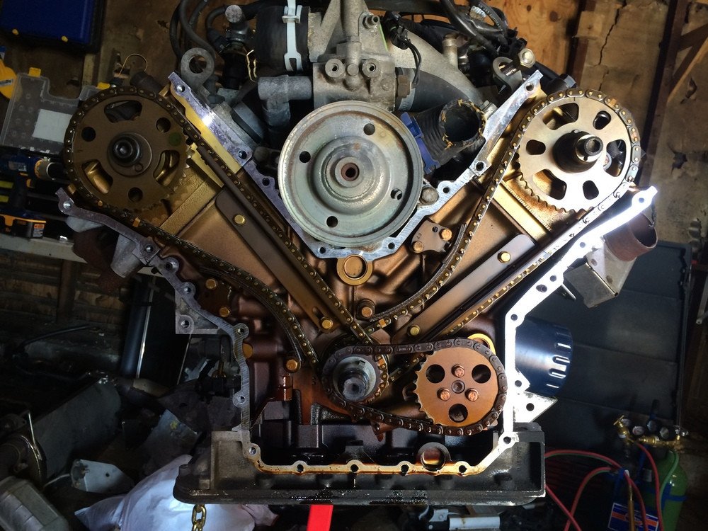 The timing cover removed, revealing the golden internals of the 3.0L engine.