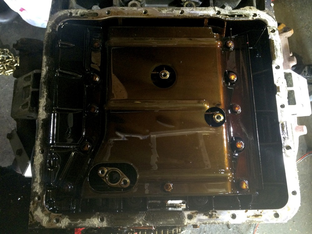 The oil baffle under the inlet pipe. The oblong piece on the lower-left corner of the image has an O-ring that should be replaced before re-assembly.