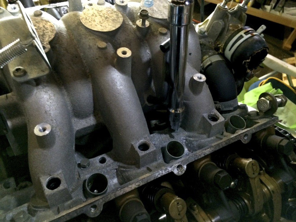 Removing the intake manifold's bolts with an 11mm socket.
