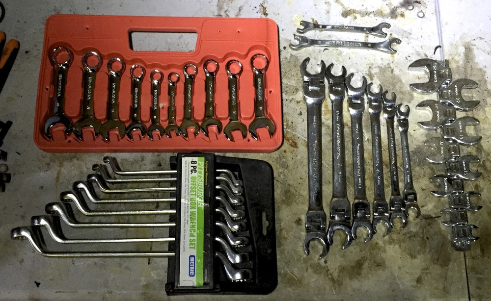 Various specialty wrenches:  stubby (top left), offset (bottom left), ratcheting open ended (top right), tilt-head (middle right), and crows feet (right).
