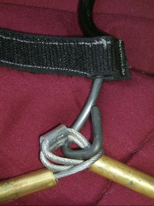 A piece of velcro is sewn around the neck, providing a built-in wrap to keep the collapsed coat hanger held in place.  An alluminium ferulle is used to keep the cable together, with the ends pushed back into the tube.