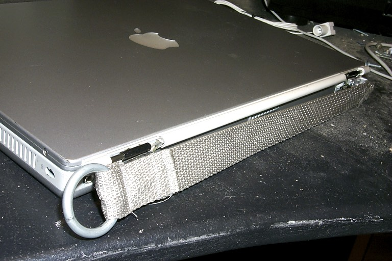 The new mount attached to the laptop, ports covered.