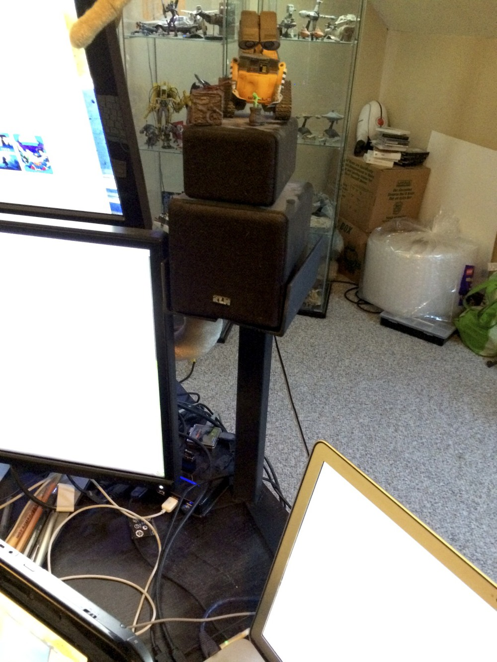 The right speaker stand sits between the stacked monitors and my MacBook Pro.