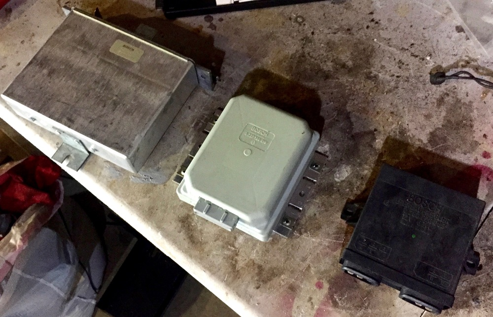 All three ECUs removed from the car: lambda (left, silver), ignition (center, grey) and idle (right, black).