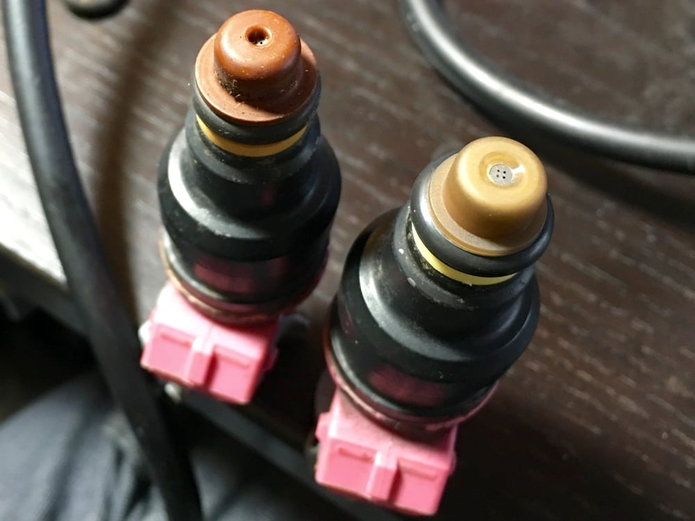 An injector with an old cap (left) and a new, noticeably more flush cap (right).