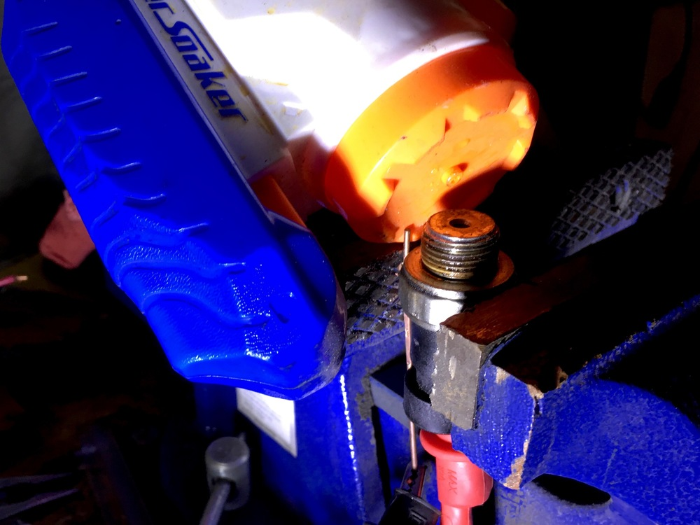 Positioning the Super Soaker nozzle over the end of the 3.0L oil pressure switch for bench testing.