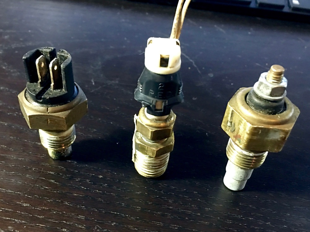 The 3.0L coolant temperature gauge sender (left), the 2.8L one (right), and an alternate sender from the water pump (middle).