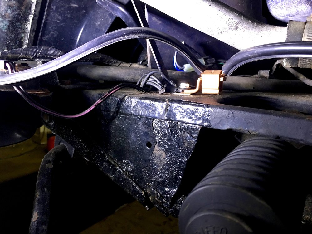 The lug bolted to the front frame extension, along with the radiator bracket and the existing ground wire bundle.