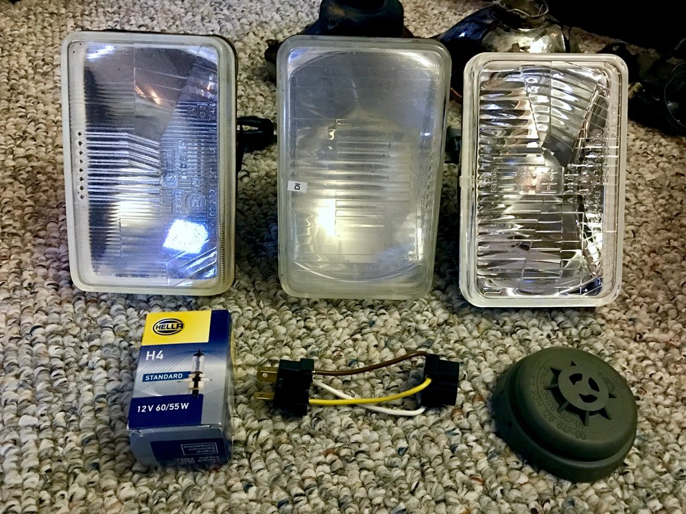 The old fogged (due to micro-scratches) lenses (left and center) and the new Hela lens (right).  The sense also included an H4 bulb (bottom left), an adaptor pigtail (bottom center) and a rubber plug that I didn't install.