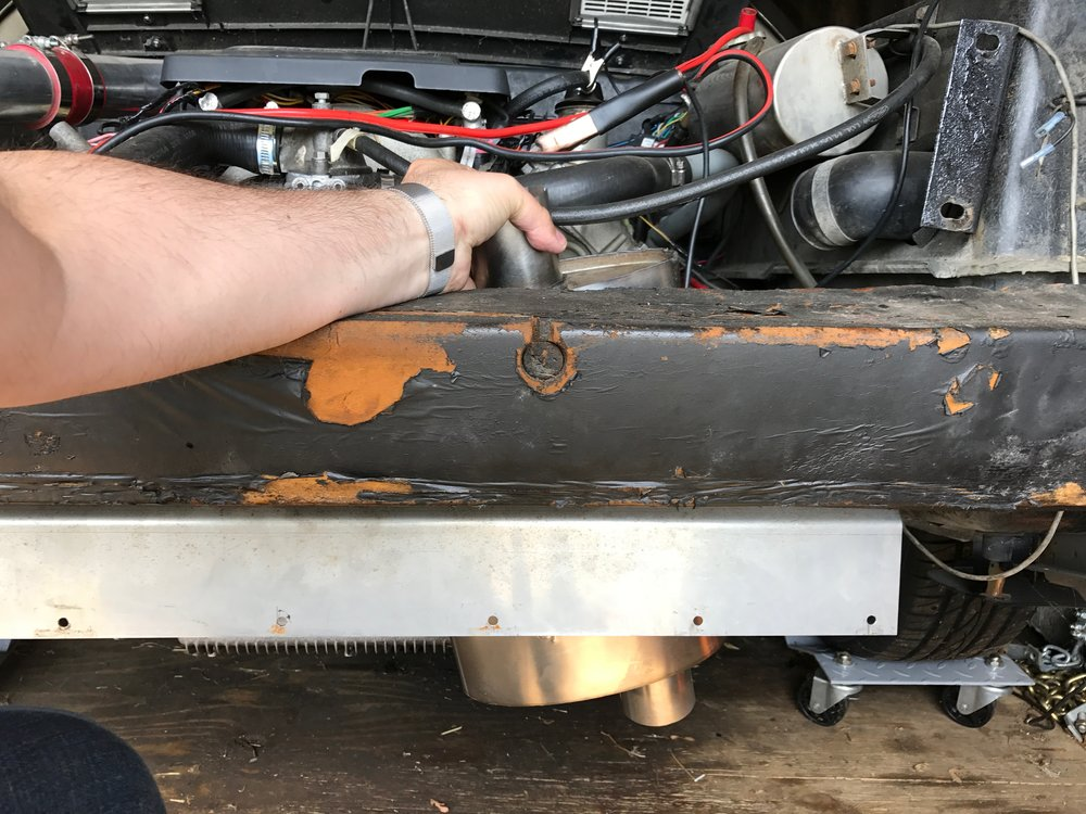 A test fit showing how badly my original muffler plan worked. The muffler needed to be mounted at about a 45 degree angle, and was too big to fit. The tail pipes need to come out next to the metal shield under the bumper.