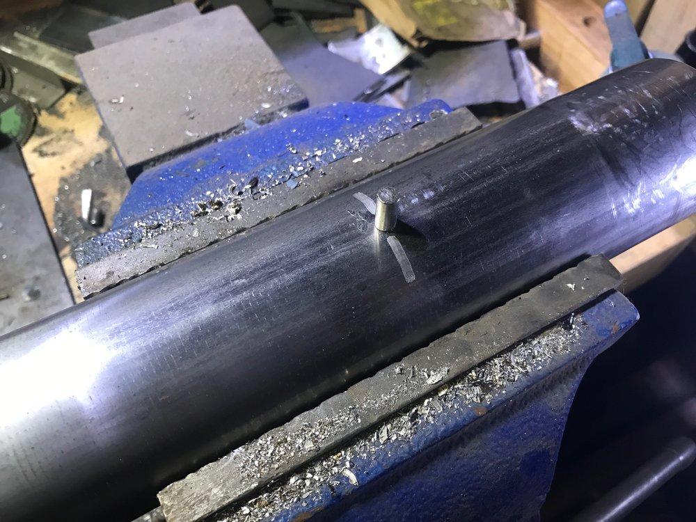 Using a magnet to mark the location of the insert inside the stainless steel pipe.