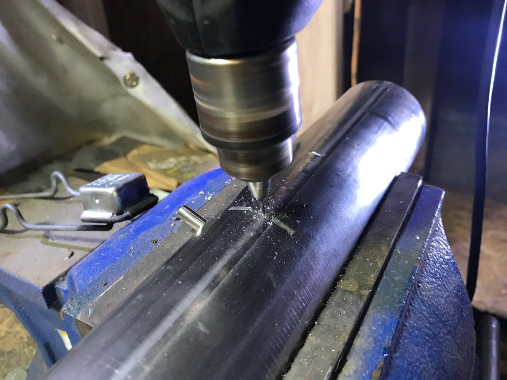 Drilling a hole through both the pipe and the silencer at the same time.