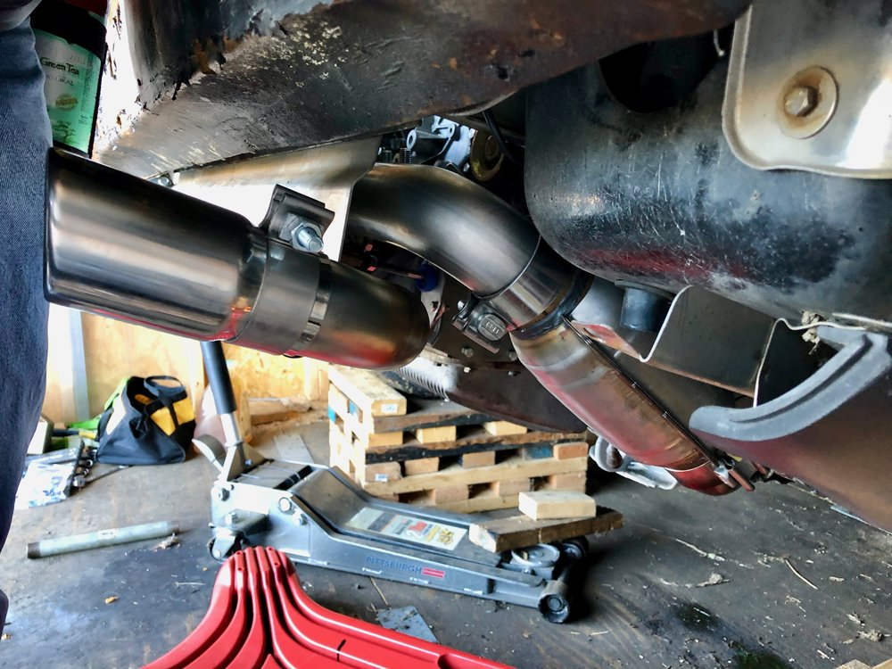 The passenger side exhaust tip, whose pipe comes out of the bottom of the muffler.