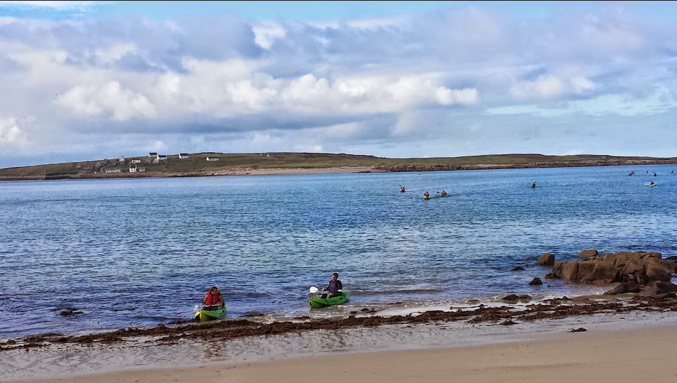 Kayakers return from their sea adventure around the back of Inish Méan, exploring the coastilne, caves and sea arches.