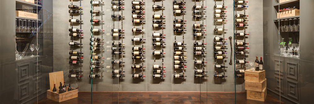 Wine Room ( Gallery).  This room was designed to have the wine become an art object in the home.    This room was also a shell of a space.  The espresso room was originally conceived to  be the wine room. The homeowner did not want that large of a space dedicated to wine and was more interested in coffee and the concept of having an espresso room.  He loved the idea of having wine stored in an unexpected place and an unexpected way.   We carved an area out that had no defined purpose and decided to create a wine wall.  There was a soffit that existed in the space and i extended that soffit out further into the room in order to create the illusion of having the wine area dug out of the room.   To add to that illusion, i painted the entire area dark with the tile and cabinetry to closely match.  The tile utilized on the back wall is a porcelain metallic to give some depth to the space.   The racks were custom made in chrome to add a flash.  Starfire glass encloses the space.