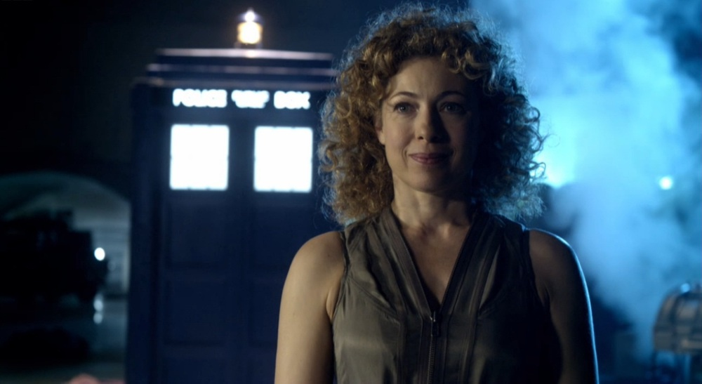 River Song stands in front of the TARDIS.