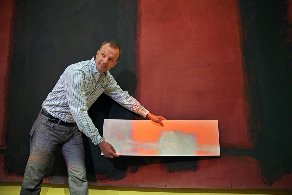 A conservator demonstrating the effect of the projection with a poster board