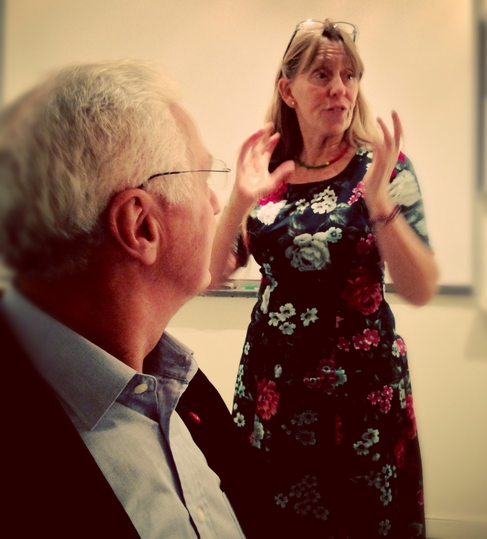 Annika förklarar för den ätande hopen hur konstlotterier bör arrangeras för att inte orsaka skoskav.