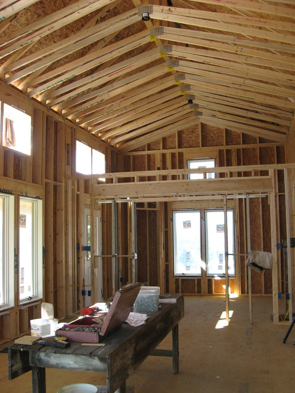 During:  even though the home's profile had to be kept modest so as not to dominate the daughter's house behind, my client still wanted high ceilings and light.  The awning windows are above the outside porch roof, and the wall between the Great Room and the Study/Guest Bedroom does not extend to the ceiling.  This allows you to see the windows at each gable end, from each room.  Nice air flow too.