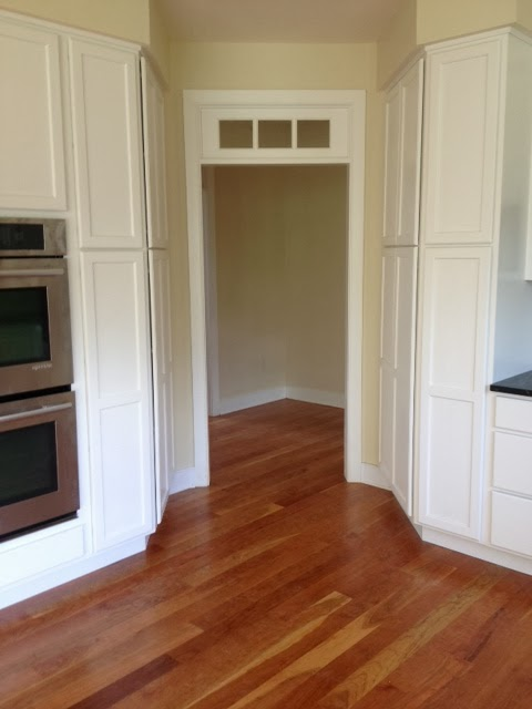 The doorway off the corner of the kitchen leads to a hallway which accesses both the master suite and a small rear mudroom area.  The transom is a special touch and aligns horizontally with the the window heads, and also the cased opening's trim between the dining room and the living room. Note the pantry cabinets tucked in on each side of this doorway.  Every inch of this house was important!