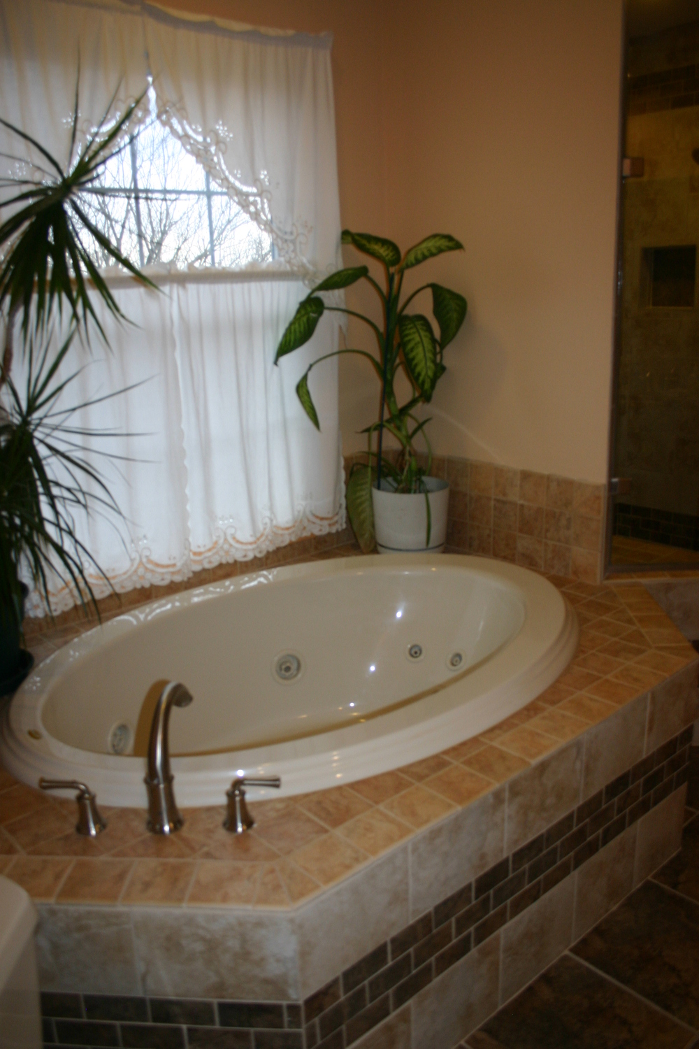 AFTER: the original tub was replaced by a modern smaller tub with a tiled platform.  This gave the clients the opportunity to have a much larger shower.