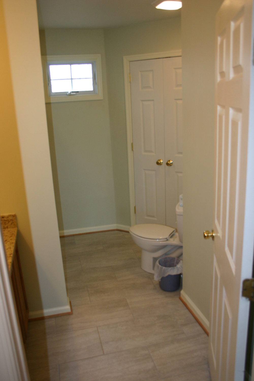 AFTER:  This toilet backs up to the new master bath one, on an angled wall that gives the toilet/tub area much more floor space.  Bonus:  room in the corner for a much-needed linen closet.