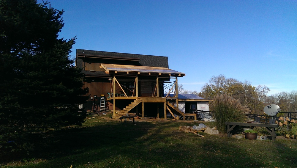 DURING:  The back deck's been enlarged substantially and the roof is being added.  Careful planning throughout