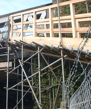 Scaffolding supports the wooden walkway