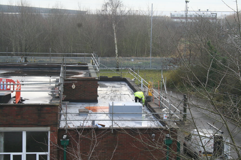 A member of the team working on a flat roof
