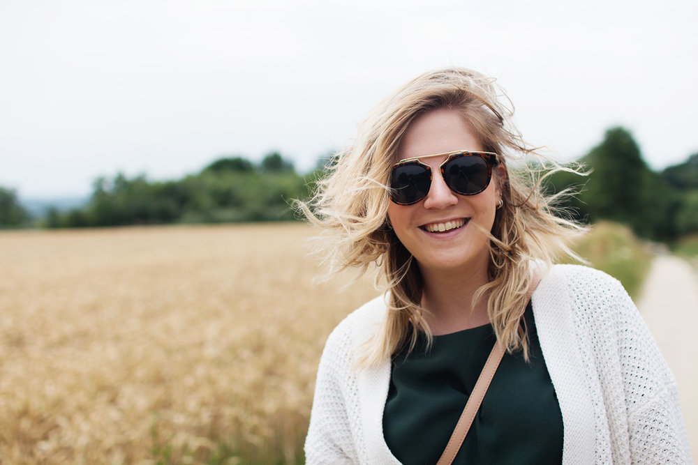 Smiling woman wearing sunglasses in front of wheat field