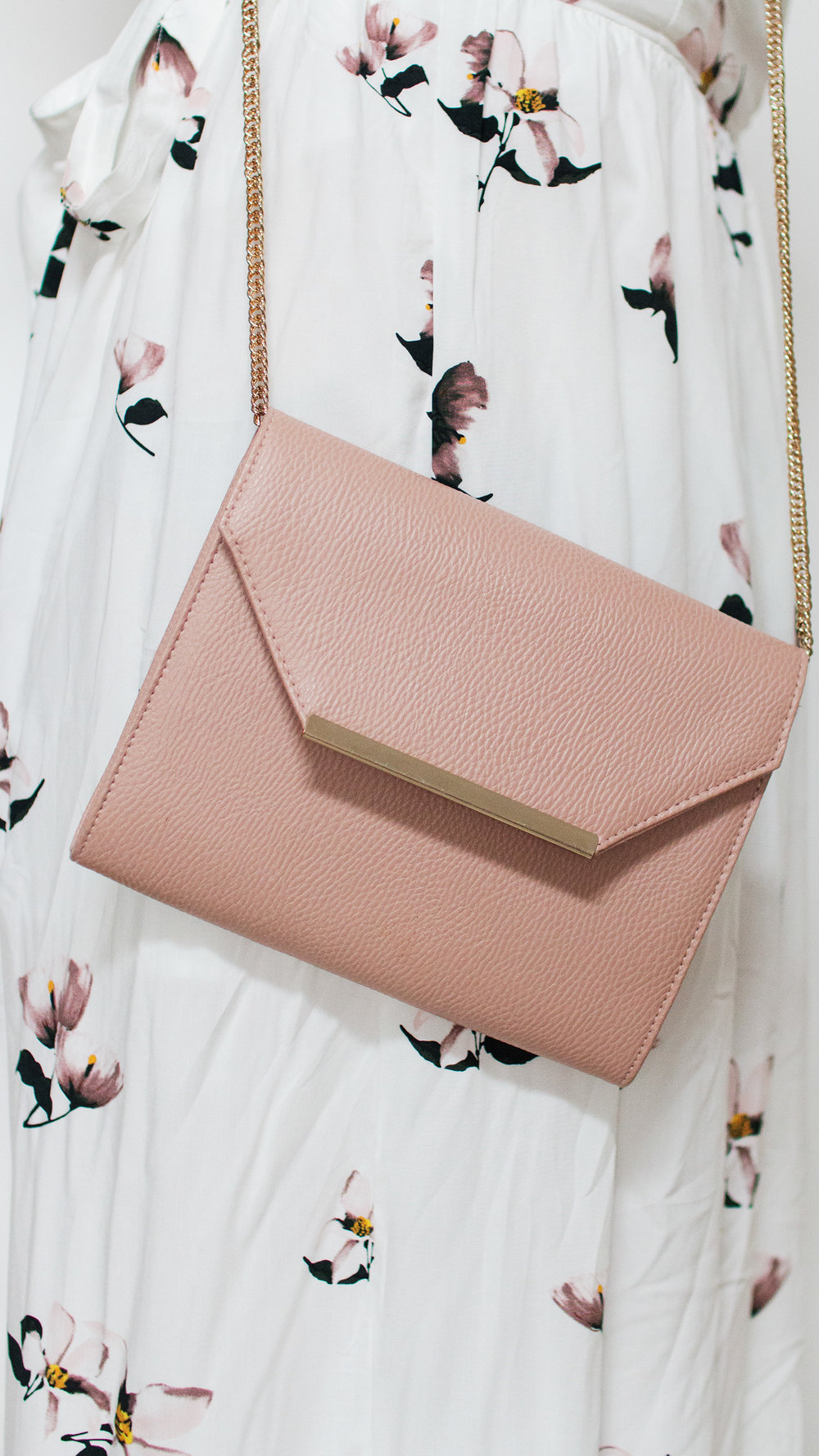 Blush coloured clutch bag against white floral dress