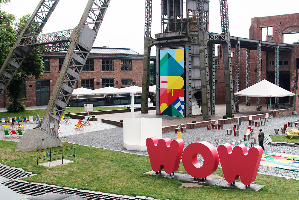 "C-mine in Genk, with colourful exhibition in the garden and red giant letters saying ""WOW"""