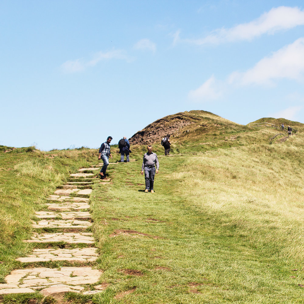 People walking up a hill in the Peak District