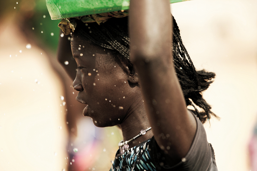 YOUNG GIRL CARRIES WATER