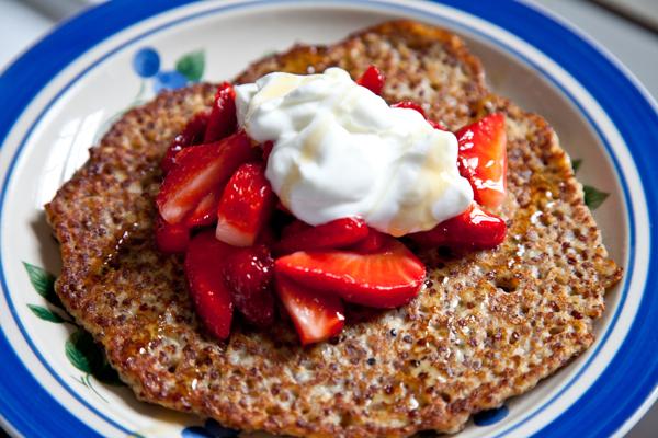 red quinoa pancakes served with fresh strawberry slices, greek yogurt and honey