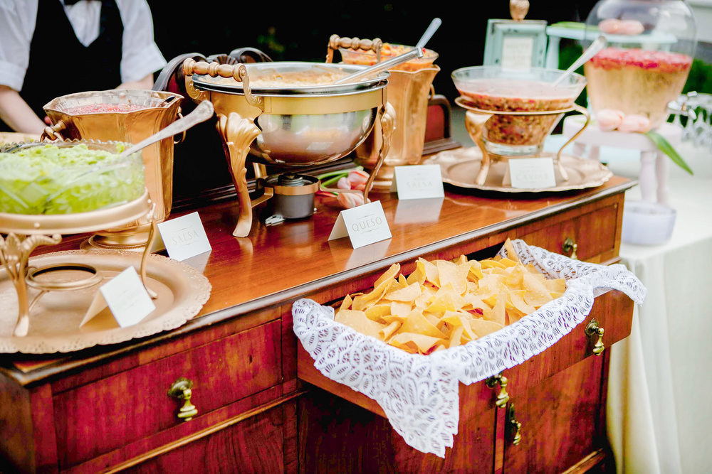 A south of the border station with fresh tortilla chips, a variety of salsas, queso. it alsoincluded a chef preparing fresh guacamole for guests and was made complete with red and white wine sangria.