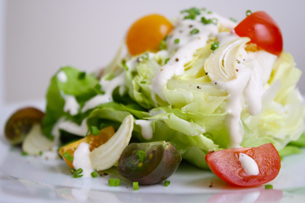 wedge salad with garlic chips, tomatoes and raw ranch dressing