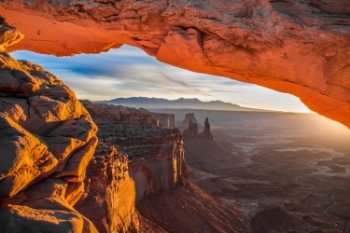 Photographers and nature enthusiasts come from around the globe to photograph the famous mesa at sunrise in Canyonlands National Park in Moab. The sun illuminates the underbelly of the mesa, creating a dramatic fiery appearance.