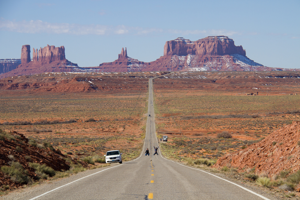 Cute couple taking selfies along the iconic  US-163 N with Monument Valley in the background.