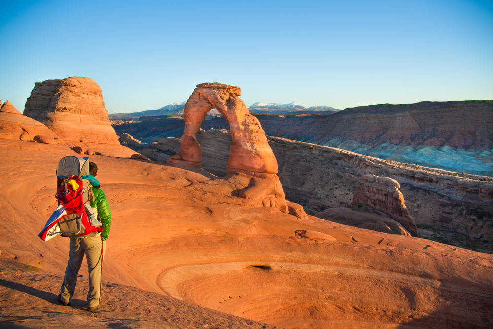 A Chinese tourist and his baby admire the view at the Delicate Arch in Arches National Park, Moab, Utah.