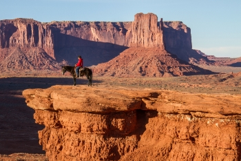 A Navajo man sits on his horse Pistol overlooking the Monument Valley. This cliff overlook is John Ford's Point, named after the famous Hollywood director who shot seven western movies in Monument Valley, including several with the actor John Wayne.