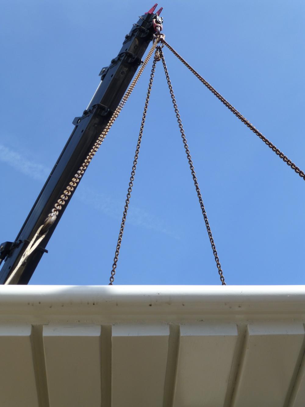 De kraanwagen hees het met kettingen omhoog en slierde het dak traag tot boven het wachthuisje