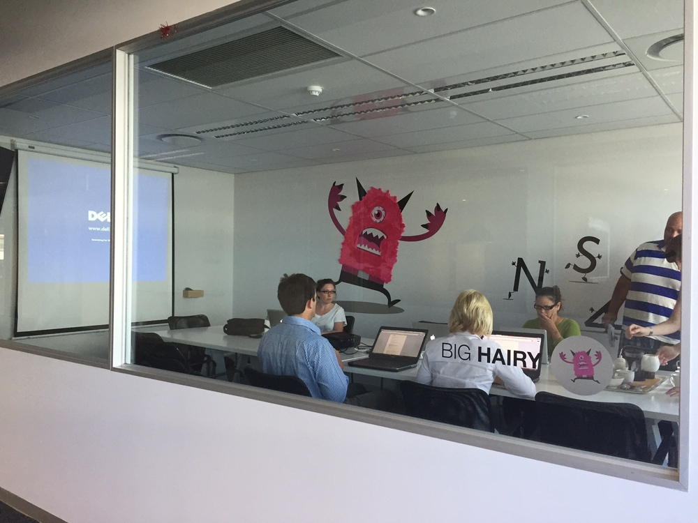 The Big Hairy meeting room describes our big hairy audacious goal, which is to have more impact than UNISA by 2024. The room has the big, angry GetSmarter monster chasing after a jumbled up UNISA running away in the right of the image.