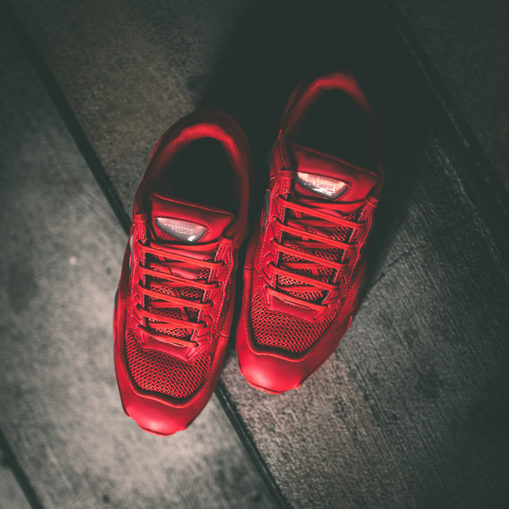 Raf Simmons x Adidas Ozweego 2 has an all-new color way. Features a synthetic mesh upper and AdiPrene Technology in the midsole. The Ozweego is an intricate and modern silhouette that stands out in a vibrant red. Three lines mark the back heel to add the Adidas logo and the light red silicone bubbles incorporate the monochromatic tones of red throughout the shoe.Purchase your pair now, in store and online at Epitome.