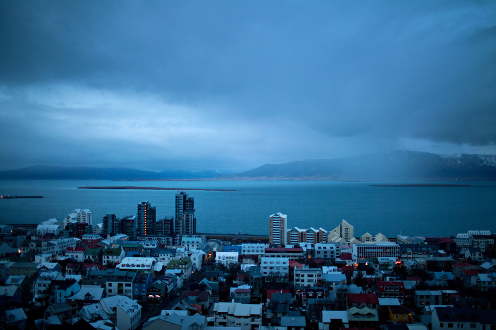 A light drizzle sprinkles the sea off of Reykjavik. On the waterfront, unfinished luxury apartments loom over the city.