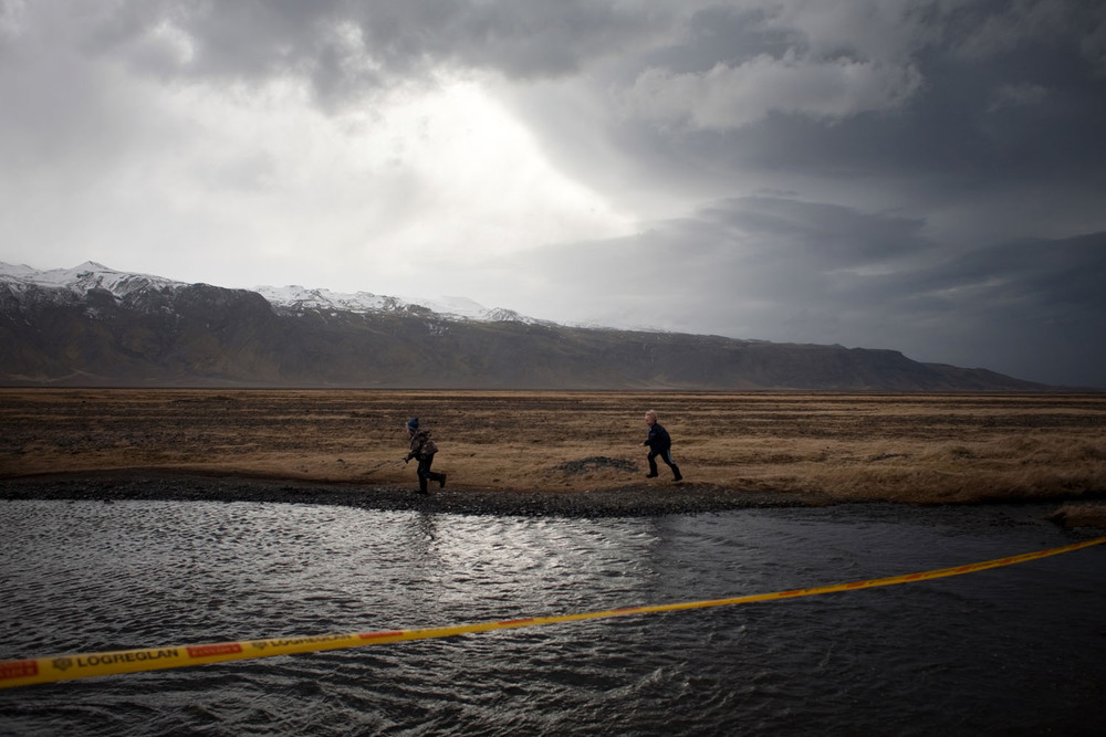 Police tape warns of impending flooding as a result of the first eruption in Eyjafjällajökull. Einar Jón and Thorarinn Helgi play around it.