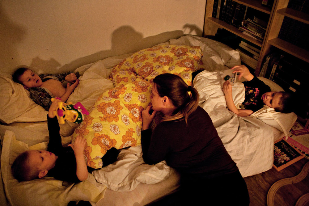 Arndís Tómasdóttir tucking in her grandchildren, who are home for the holidays, on a mattress in her home office.
