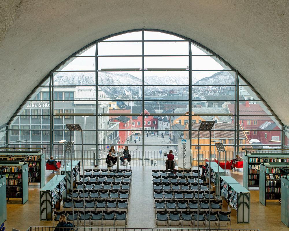 Tromsø bibliotek og byarkiv  Biblioteknr.: NO-2190200 Tromsø, Troms Fotografert: 2015  Tromsøs hovedbibliotek har siden 2005 holdt hus i den ombygde Fokus Kino sentralt i byen. Bygget ble tegnet av arkitektGunnar Bøgeberg Haugenog åpnet i 1973.Siden 2015 har tromsøværinger også kunnet låse seg inn på biblioteket med lånekortet sitt utenom betjent åpningstid, et tilbud som finnes på stadig flere biblioteker rundt om i landet.