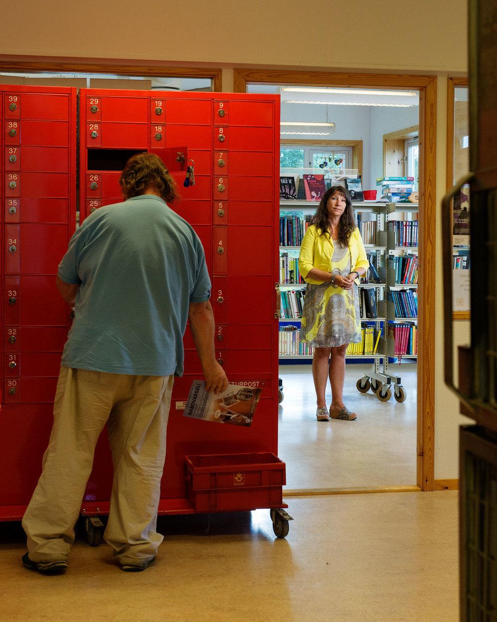 Hobøl bibliotek   Biblioteknr.: NO-2013800 Hobøl, Østfold Fotografert: 2016  «Posten har flytta mange ganger. Gjensidige hadde Posten sist, men ville ikke fortsette med det fordi det ble for kostbart. Det samme sier Kiwi. At det skal bli noe billigere for oss å ha Posten, det klarer ikke jeg å se. Etter at vi ble postkontor har vi fått så mye kjeft som vi aldri har fått før, fordi vi har måttet endre åpningstidene. Men det verste var kanskje at Posten tok arealet vårt. Vi hadde en fin lesesal og god plass til arrangementer.»   Kristin Lippestad. Etter at Posten flyttet inn i biblioteket, ble hun biblioteksjef, kultursjef og postsjef i Hobøl kommune.