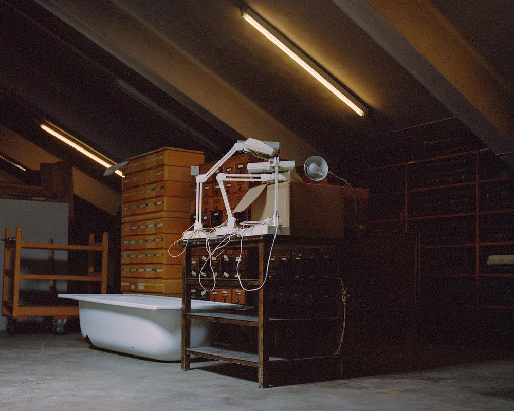 Deichmanske bibliotek, Hovedbiblioteket   Biblioteknr.: NO-2030000 Oslo  Fotografert: 2015  Hovedbiblioteket i Oslo flytter snart til nye lokaler i Bjørvika. Da forsvinner mange av bokmagasinene, og det meste av boksamlingen skal være synlig for publikum. Fremtidens bibliotek skal ha færre bøker. Overfylte magasiner rundt om i landet skjuler sjeldne, gamle bøker, men også teknologi som har gått ut på dato og annet skrot, slik som på loftet til Deichmanske hovedbibliotek.